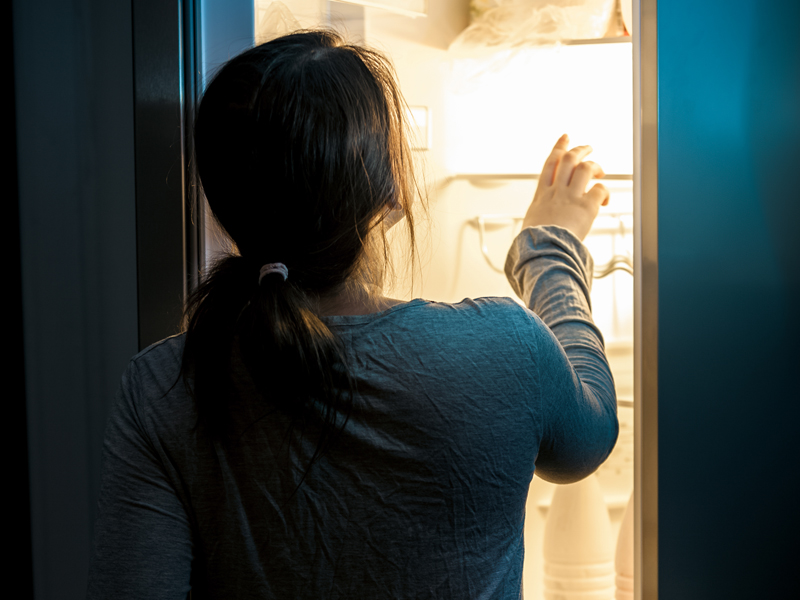 Woman looking in fridge at night